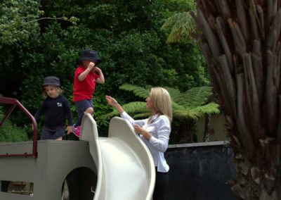 Vision and values gallery, Maria assists children playing on the slide