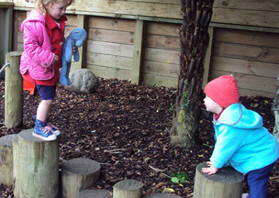 Environment Design gallery, two children playing together on tree stumps