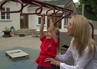 About Page Gallery, Maria assisting a child on the monkey bars