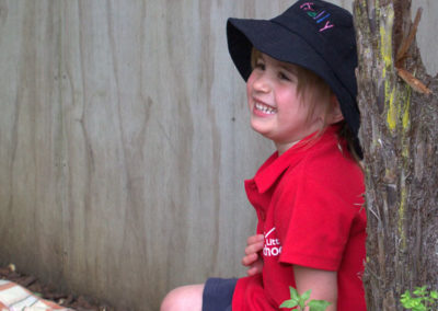 About page gallery, smiling child sitting by a tree